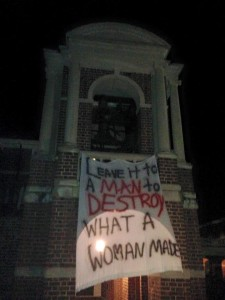 """Leave it to a man to destroy what a woman made"" - banner hanging on the bell tower."