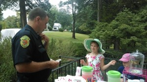 Children of alumnae sold lemonade, donuts, cookies and art to benefit their Mom's College. In this photo, Joan Dabney Clinker's daughter sells a donut to campus security.